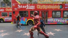A tourist snaps a picture of a man dressed as an action movie character on  Hollywood Boulevard on March 7, 2013 in Hollywood, California.    AFP PHOTO / JOE KLAMAR        (Photo credit should read JOE KLAMAR/AFP/Getty Images)